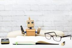 Το ρομπότ κάθεται στον πίνακα και κρατά μια μάνδρα για το γράψιμο στοκ εικόνα με δικαίωμα ελεύθερης χρήσης