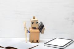 Το ρομπότ κρατά μια μάνδρα και το τηλέφωνο είναι κοντά στο lap-top εργασία στοκ φωτογραφία με δικαίωμα ελεύθερης χρήσης