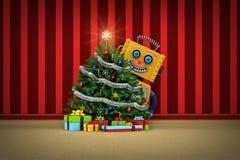 Το ρομπότ παιχνιδιών ευχαριστημένο από το χριστουγεννιάτικο δέντρο και παρουσιάζει Στοκ Εικόνες