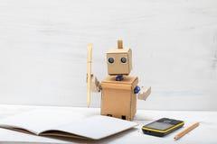 Το ρομπότ που κρατά μια μάνδρα και έγραψε σε ένα σημειωματάριο η διαδικασία εργασίας Στοκ Εικόνες