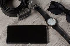 Το ρολόι, ζώνη δέρματος, πωλεί το τηλέφωνο, γυαλιά ηλίου σε μια γκρίζα ξύλινη ΤΣΕ Στοκ εικόνες με δικαίωμα ελεύθερης χρήσης