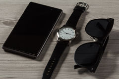 Το ρολόι, πωλεί το τηλέφωνο, γυαλιά ηλίου σε ένα γκρίζο ξύλινο υπόβαθρο Στοκ Εικόνες
