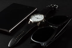 Το ρολόι, πωλεί το τηλέφωνο, μαύρα γυαλιά ηλίου σε ένα μαύρο υπόβαθρο Στοκ Εικόνες