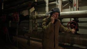 Το ρωσικό άτομο σε ένα καπέλο με τα earflaps, που μιλούν στο τηλέφωνο σε ένα σκοτεινό υπόγειο και αποφασίζει τα θέματα εθνικής σπ φιλμ μικρού μήκους