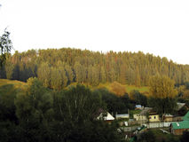 Το ρωσικό χωριό βρίσκεται μεταξύ των λόφων στοκ φωτογραφία