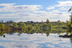 Το ρωσικό χωριό και οι πράσινοι τομείς με τα δέντρα και ένας μπλε ουρανός με τα σύννεφα απεικόνισαν στο ήρεμο νερό της λίμνης Ηρε Στοκ Εικόνες
