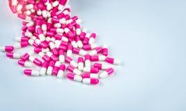 Το ρόδινο και άσπρο χάπι καψών ανέτρεψε έξω από το άσπρο πλαστικό εμπορευματοκιβώτιο μπουκαλιών r Φάρμακο αντιβιοτικών στοκ εικόνα με δικαίωμα ελεύθερης χρήσης