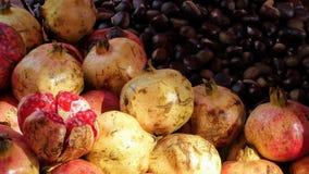 Το ρόδι και τα κάστανα σε μια αγορά οδών, ένα από τα φρούτα ανοίγονται για να αποκαλύψουν το ρόδι μέσα στοκ εικόνα με δικαίωμα ελεύθερης χρήσης