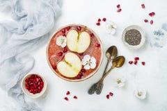 Το ρόδινο κύπελλο καταφερτζήδων superfoods με τους σπόρους chia, ρόδι, τεμάχισε τα μήλα και το μέλι Η υπερυψωμένη, τοπ άποψη, επί Στοκ φωτογραφία με δικαίωμα ελεύθερης χρήσης