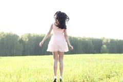 Το ρόδινο φόρεμα κοριτσιών πηδά το καλοκαίρι λιβαδιών, ιδέα έννοιας ευτυχίας της διασκέδασης, χαρά ήλιων αριθμού χαλάρωσης Στοκ εικόνα με δικαίωμα ελεύθερης χρήσης