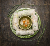 Το ρύζι κυλά με ένα διαφανές νουντλς μέσα στα φύλλα του κρεμμυδιού και του φυτικού ζωμού στη σκοτεινή ξύλινη αγροτική τοπ άποψη υ Στοκ φωτογραφία με δικαίωμα ελεύθερης χρήσης
