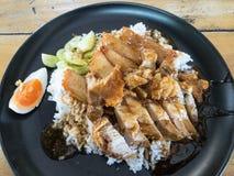 Το ρύζι με το ψημένο χοιρινό κρέας και το τσιγαρισμένο χοιρινό κρέας στην κορυφή, εξυπηρετεί στο μαύρο πιάτο στοκ εικόνα