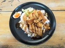 Το ρύζι με το ψημένο χοιρινό κρέας και το τσιγαρισμένο χοιρινό κρέας στην κορυφή, εξυπηρετεί στο μαύρο πιάτο στοκ φωτογραφία
