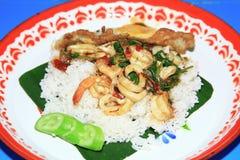 Το ρύζι που ολοκληρώνεται με τα ανακατώνω-τηγανισμένους θαλασσινά και το βασιλικό με το τηγανισμένο αυγό στο μεγάλο δίσκο, ταϊλαν Στοκ εικόνα με δικαίωμα ελεύθερης χρήσης