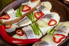 Το σάντουιτς με τις ρέγγες, ο καφετής Tommy, μαρινάρισε το αγγούρι, το κρεμμύδι και το πιπέρι Στοκ εικόνες με δικαίωμα ελεύθερης χρήσης