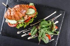Το σάντουιτς Croissant με τη λωρίδα έψησε το κοτόπουλο, τα φρέσκα λαχανικά, το τυρί και τα πράσινα στον πίνακα μαύρου σχιστόλιθου στοκ φωτογραφίες με δικαίωμα ελεύθερης χρήσης