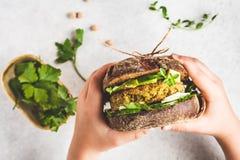 Το σάντουιτς Vegan με chickpea patty, το αβοκάντο, το αγγούρι και τα πράσινα στη σίκαλη πασπαλίζουν με ψίχουλα στα χέρια των παιδ στοκ εικόνα