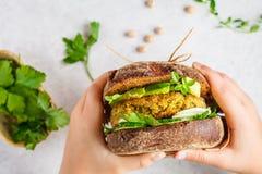 Το σάντουιτς Vegan με chickpea patty, το αβοκάντο, το αγγούρι και τα πράσινα στη σίκαλη πασπαλίζουν με ψίχουλα στα χέρια των παιδ στοκ φωτογραφία