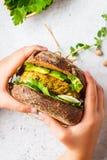 Το σάντουιτς Vegan με chickpea patty, το αβοκάντο, το αγγούρι και τα πράσινα στη σίκαλη πασπαλίζουν με ψίχουλα στα χέρια των παιδ στοκ εικόνες