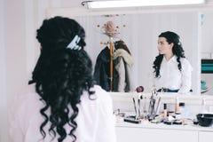 Το σαλόνι ομορφιάς, κορίτσι με τη μακριά μαύρη τρίχα κάθεται στον καθρέφτη στο στούντιο ομορφιάς Στοκ Φωτογραφίες