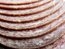 Το σαλάμι τεμαχίζει την κινηματογράφηση σε πρώτο πλάνο - επεξεργασμένα τρόφιμα - σαλάμι χοιρινού κρέατος Στοκ Εικόνες