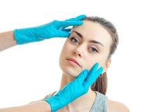 Το σαλόνι ομορφιάς Beautician κρατά τα νέα κορίτσια προσώπων στα μπλε-φορημένα γάντια χέρια Στοκ εικόνες με δικαίωμα ελεύθερης χρήσης