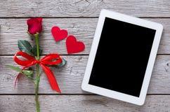 Το σε απευθείας σύνδεση υπόβαθρο διακοπών αγορών, οθόνη ταμπλετών, αυξήθηκε καρδιές λουλουδιών και εγγράφου στο αγροτικό ξύλο Στοκ Φωτογραφία