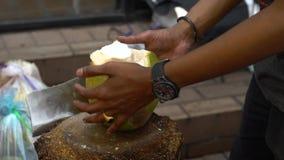 Το σε αργή κίνηση άτομο προμηθευτών κόβει με το μαχαίρι μια πράσινη καρύδα Οδός αγοράς φιλμ μικρού μήκους
