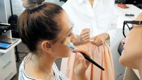 Το σε αργή κίνηση βίντεο κινηματογραφήσεων σε πρώτο πλάνο του θηλυκού visagiste που ισχύει makeup στα πρότυπα αντιμετωπίζει στο ε φιλμ μικρού μήκους