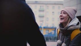 Το σε αργή κίνηση ευτυχές χαμογελώντας νέο ευρωπαϊκό κορίτσι το χειμώνα ντύνει τους περιπάτους έξω κατά μια ημερομηνία με τα χέρι απόθεμα βίντεο