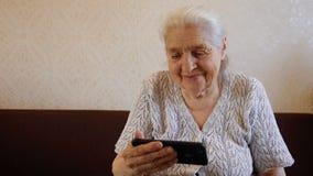 Το σε αργή κίνηση πορτρέτο ευτυχούς είναι μια ηλικιωμένη γυναίκα που χρησιμοποιεί το smartphone και το χαμόγελο απόθεμα βίντεο