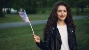 Το σε αργή κίνηση πορτρέτο του όμορφου ευτυχούς αμερικανικού σπουδαστή κοριτσιών που κυματίζει τις ΗΠΑ σημαιοστολίζει, εξέταση τη φιλμ μικρού μήκους