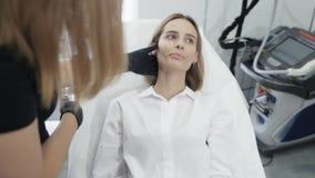Το σε αργή κίνηση beautician στο πρόσωπο αφής γαντιών του κοριτσιού, εξετάζει τις ζώνες για την επεξεργασία και τις ιατρικές διαδ απόθεμα βίντεο
