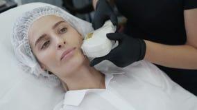 Το σε αργή κίνηση cosmetologist κάνει τη διαδικασία κοριτσιών για το δέρμα προσώπου αναζωογόνησης με την ειδική συσκευή απόθεμα βίντεο