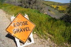 Το σημάδι οδοποιίας προειδοποιεί τους οδηγούς για το χαλαρό αμμοχάλικο μπροστά στοκ εικόνες