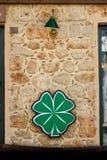 Το σημάδι 4 νέου κάλυψε το τριφύλλι, σε έναν τοίχο πετρών με σεντόνι κάτω από έναν πράσινο λαμπτήρα Στοκ Φωτογραφίες