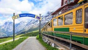 Το σημάδι της αφετηρίας για να αρχίσει το μονοπάτι για βάδισμα με την άποψη των ελβετικών σιδηροδρόμων wengernalpbahn εκπαιδεύει  Στοκ Φωτογραφία