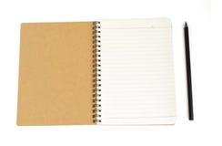 Το σημειωματάριο από το ανακύκλωσης έγγραφο και το μαύρο μολύβι απομονώνουν στα άσπρα WI Στοκ Φωτογραφία