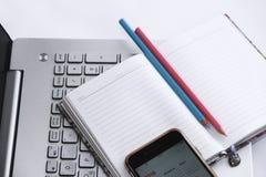 Το σημειωματάριο για την επιχείρηση με τα άσπρα φύλλα και τα μολύβια στο υπόβαθρο ενός υπολογιστή πληκτρολογούν και ένα τηλέφωνο στοκ φωτογραφίες με δικαίωμα ελεύθερης χρήσης