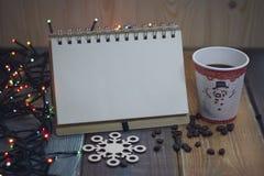 Το σημειωματάριο και το γυαλί σε έναν ξύλινους πίνακα Χριστουγέννων και ένα α Στοκ Εικόνες