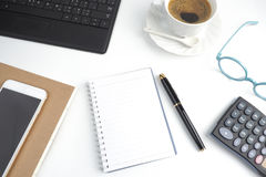 Το σημειωματάριο κενών σελίδων στον άσπρο υπολογιστή γραφείου με τη μάνδρα, καφές, lapto στοκ εικόνες με δικαίωμα ελεύθερης χρήσης