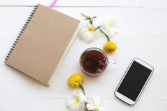 Το σημειωματάριο, το κινητό τηλέφωνο και τα βοτανικά υγιή ποτά καυτά αυξήθηκαν νερό κοκτέιλ τσαγιού στοκ φωτογραφία με δικαίωμα ελεύθερης χρήσης