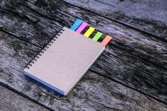 Το σημειωματάριο με την ετικέττα σημειώσεων χρωμάτων στον ξύλινο πίνακα για προσθέτει το messa κειμένων Στοκ Φωτογραφίες