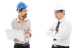 Το σημειωματάριο μπλε κρανών ατόμων δύο μηχανικών συμβουλεύεται στοκ εικόνα