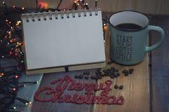 Το σημειωματάριο, το μπλε φλυτζάνι και η επιγραφή παντρεύουν τα Χριστούγεννα Στοκ Εικόνα