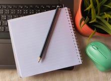 Το σημειωματάριο που ευθυγραμμίζει πέρα από το lap-top με το μολύβι, λίγα Στοκ Φωτογραφίες