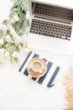 Το σημειωματάριο, το lap-top, ένα φλιτζάνι του καφέ και άσπρα λουλούδια μεγάλα ανθοδεσμών στο πάτωμα σε μια άσπρη γούνα καλύπτουν Στοκ Εικόνα