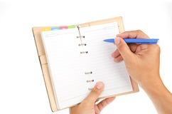 το σημειωματάριο χεριών γράφει Στοκ Φωτογραφία