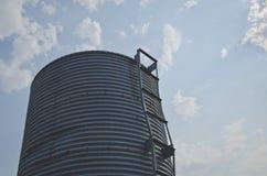 Το σιλό μετάλλων στον ουρανό στο παλαιό αγρόκτημα στοκ φωτογραφία