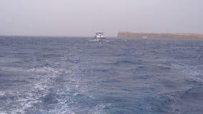 Το σκάφος αναψυχής με τους τουρίστες πλέει στη θάλασσα θύελλας στο υπόβαθρο των βράχων Αίγυπτος απόθεμα βίντεο